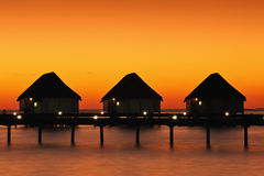 Tropical sunset with water villas Stock Photos