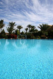 Swimming pool in Egyt, holidays. Scenic view of large blue swimming pool with tropical palm trees in background; summer vacation scene Royalty Free Stock Photos