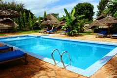 Tropical swimming pool. With huts and banana trees in background Stock Photo