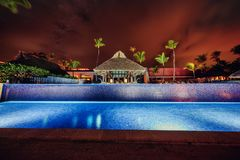Tropical swimming pool in luxury resort, Punta Cana. Tropical swimming pool and palm trees in luxury resort Stock Images