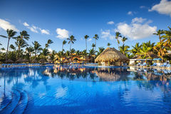 Tropical swimming pool in luxury resort, Punta Cana. Tropical swimming pool and palm trees in luxury resort Royalty Free Stock Photo