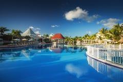 Tropical swimming pool in luxury resort, Punta Cana. Tropical swimming pool and palm trees in luxury resort Royalty Free Stock Images