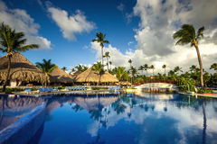 Tropical swimming pool in luxury resort at sunrise. Tropical swimming pool and palm trees in luxury resort Stock Photo
