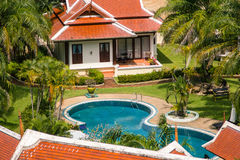Tropical swimming pool and palm trees in luxury property Stock Photo
