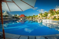 Tropical swimming pool in luxury resort, Punta Cana. Tropical swimming pool and palm trees in luxury resort Royalty Free Stock Photography
