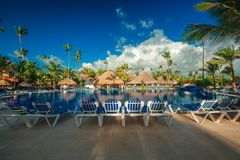 Tropical swimming pool in luxury resort, Punta Cana. Tropical swimming pool and palm trees in luxury resort Royalty Free Stock Image