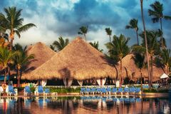 Tropical swimming pool in luxury resort, Punta Cana. Tropical swimming pool and palm trees in luxury resort Stock Photo