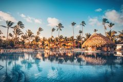 Tropical swimming pool in luxury resort, Punta Cana. Tropical swimming pool and palm trees in luxury resort Royalty Free Stock Photography