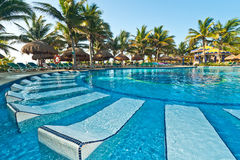 Tropical swimming pool with sunbeds Royalty Free Stock Images