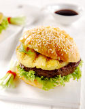 Tropical teriyaki Hawaiian pineapple burger. On a sesame bun grilled over a barbecue at a summer picnic for a tasty lunch Stock Images