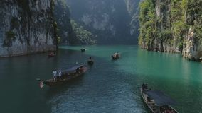 Tropical Thai jungle lake Cheo lan drone flight, wild mountains nature national park ship yacht. Tropical exotic green wild mountains sinset jungles drone 4k stock footage