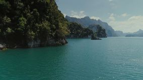Tropical Thai jungle lake Cheo lan drone flight, wild mountains nature national park ship yacht rocks. Tropical exotic green wild mountains sinset jungles drone stock footage