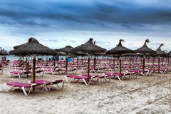 Tropical thatch umbrellas on an deserted beach in a nasty weathe. Deserted beach with sun beds and umbrellas Stock Image