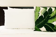 Tropical Throw Pillow on Bed. With White Sheets Royalty Free Stock Photography