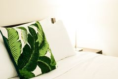 Tropical Throw Pillow on Bed. With White Sheets Stock Photo