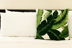 Tropical Throw Pillow on Bed. With White Sheets Stock Image