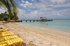 Tropical Tobago beach. A view along a beautiful tropical beach in Tobago with lounge chairs in the foreground and a dock extending into the water Stock Photography