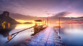 Tropical tranquil shore and pier in rays of dawn Stock Images