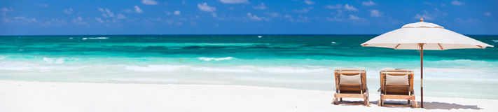 Tropical vacation. Two chairs and umbrella on stunning tropical beach in Tulum, Mexico Stock Photo