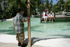 Tropical Vacation. A boy watching his mother and sister across a pool in a resort Stock Photo