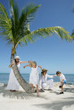 Tropical Vacation. Two women and two children enjoying their tropical vacation on a beach Stock Image