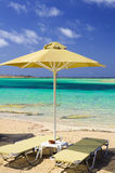 Tropical vacation - beds and umbrella on a beach Stock Photos