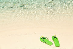 Tropical vacation concept—Green flip-flops on a sandy ocean be Stock Photos