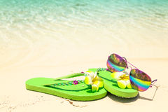 Tropical vacation concept—Green flip-flops and sunglasses on a Stock Photography
