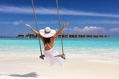 Female traveler on a swing enjoys her summer holiday royalty free stock images