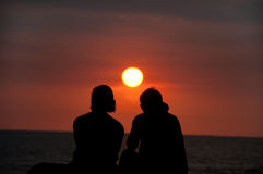 Tropical Vacation Couple on Beach Watching Sunset Royalty Free Stock Photos