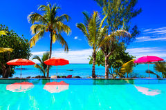 Tropical vacation - turquoise swim pool with sea view. Mauritius. Tropical holidays,view with swimming pool ,sea and palm tree.Mauritius island Stock Images