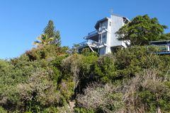 Tropical vegetation covers a hillside and almost hides steps up to a three story beach house on the top of the hill Royalty Free Stock Images