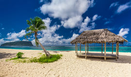 Tropical vibrant beach on Samoa Island with palm tree and fale Royalty Free Stock Photo