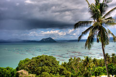 Tropical view. Beautiful view of a palm tree in the foreground and fish farms and a volcano in the background Stock Photography
