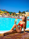 Tropical view. Attractive woman enjoing cocktail near the pool Stock Photo