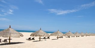 Tropical view of a beach with umbrellas and beach chairs Stock Photo