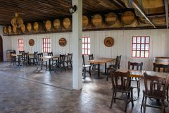 Tropical view in restaurant, Many group of wooden tables and chairs with wine barrels decorate in the room. royalty free stock image