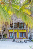 Tropical villa through palm trees at exotic beach Stock Photography