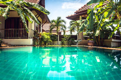 Tropical villa among palm trees at swimming pool with turquoise water Royalty Free Stock Photo