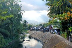 Tropical village on the banks of the river. Stock Image