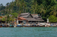 Tropical village with longboats and wooden houses under palm trees Royalty Free Stock Photo