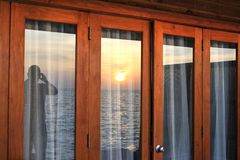 Tropical ocean sunset photograph reflected in window Stock Photos