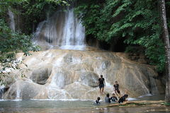 Tropical waterfall. Happy tourists have fun at the beautiful waterfall in Thailand Royalty Free Stock Images