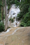 Tropical waterfall. Tourists have fun at the beautiful waterfall in Thailand Stock Image