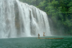 Tropical waterfall with boys on raft.