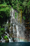 Tropical waterfall detail with rainbow. Royalty Free Stock Image