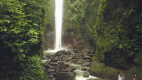 Tropical waterfall flowing from rocky mountain in rainforest aerial landscape. Traveler girl on rocky waterfall in stock footage