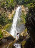 Tropical waterfall with girl hiking in front Stock Images