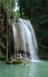 Tropical waterfall. People sitting beneath waterfall in Erawan, Thailand Stock Images
