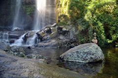 Tropical waterfall with a totem and sunray. In Petropolis, Rio de Janeiro royalty free stock photo